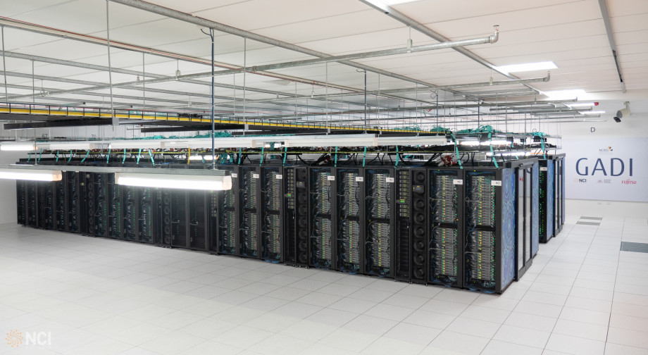 Wide picture of many rows of computer servers in a big open room, with blue artwork on one face.
