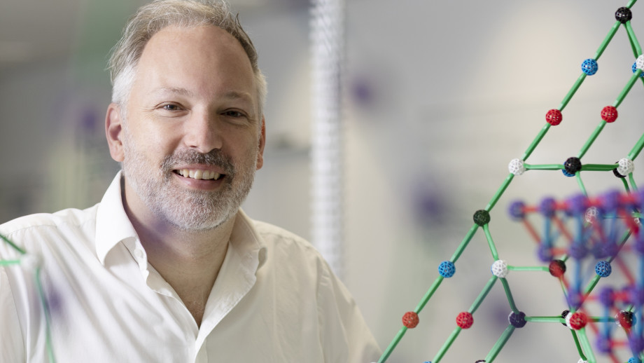 Professor Stephen Bartlett smiles at the camera with models of molecules around him.