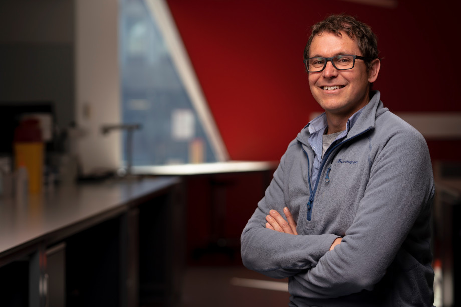 A man, Ben Corry wearing glasses and a jumper stands in a science laboratory with his arms crossed smiling at the camera.