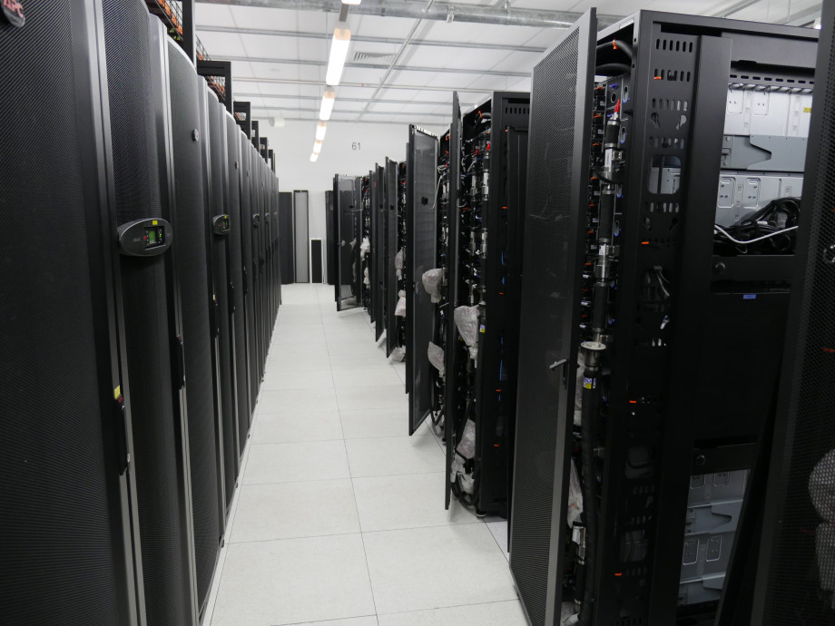 A solid row of black server racks on the left facing new, unconnected server racks on the right.