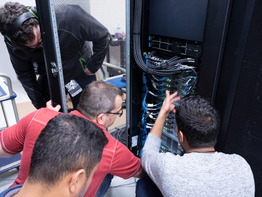Computer experts huddle around computing equipment.