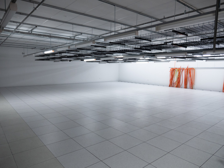 An empty space in a data centre with brand new flooring.