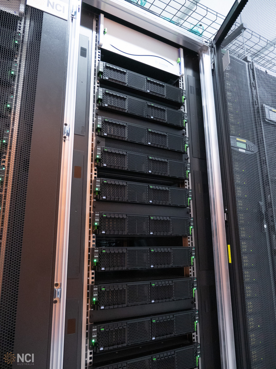 A tall stack comprising of around a dozen black and green computer servers.