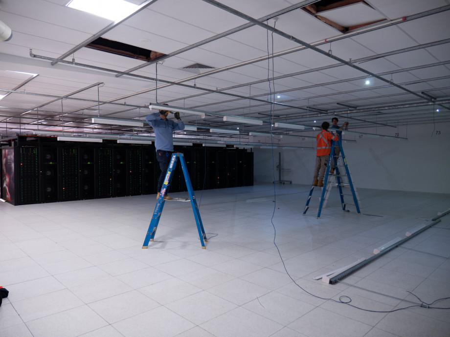 Men on ladders removing long fluorescent lights hanging from the ceiling a large room with a supercomputer in the background.