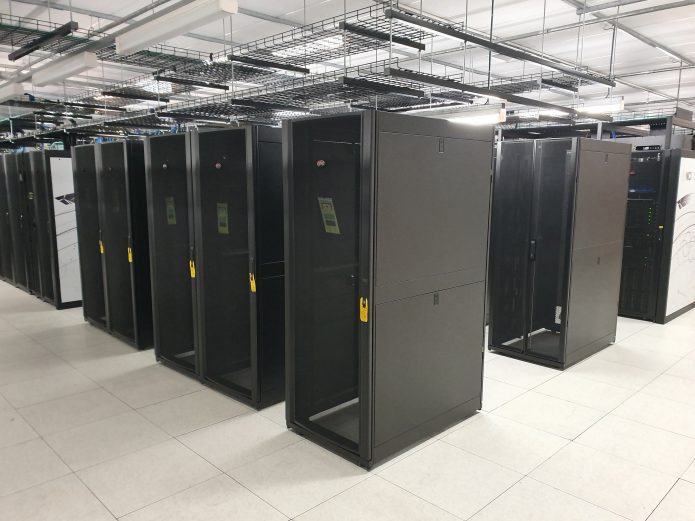 Six black server racks stand empty in rows surrounded by functioning supercomputer equipment.