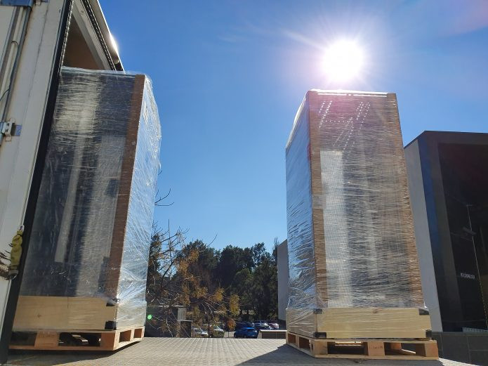 Two tall pallets wrapped in clear plastic sit on the loading bay of a delivery truck.