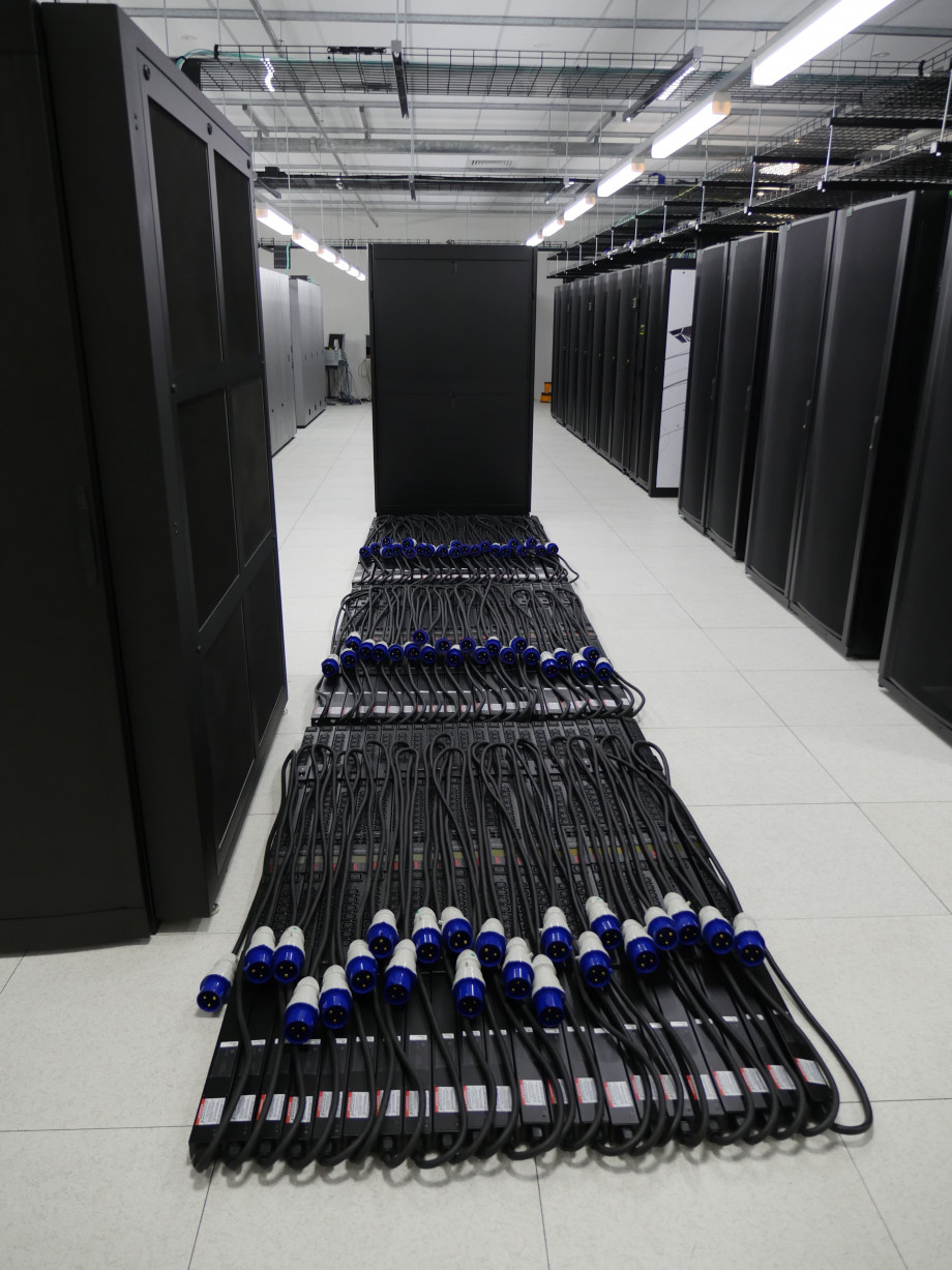 Neatly coiled thick black power cables with blue plugs lie on the floor ready for use.