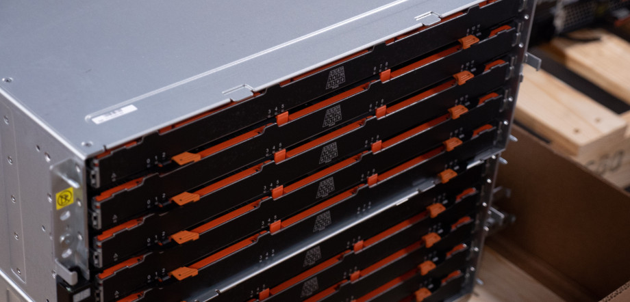 A silver box with a black front arranged in rows with orange highlights, this is a server that stores hard drives.