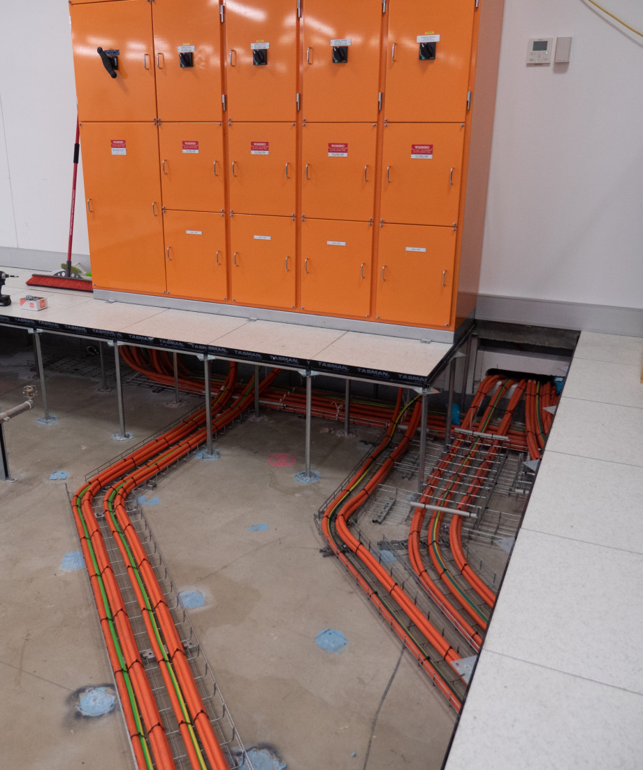 Neatly lined up orange cables in bundles run on the exposed concrete slab to connect underneath an orange electrical box.