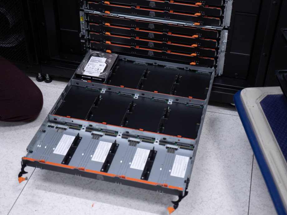 An open flat compartment with twelve rectangular slots, one of them filled with a hard drive.