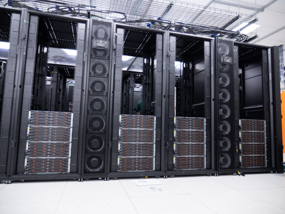 Four empty black server racks are one-third filled from the bottom up with sets of four stacked orange and black draws.