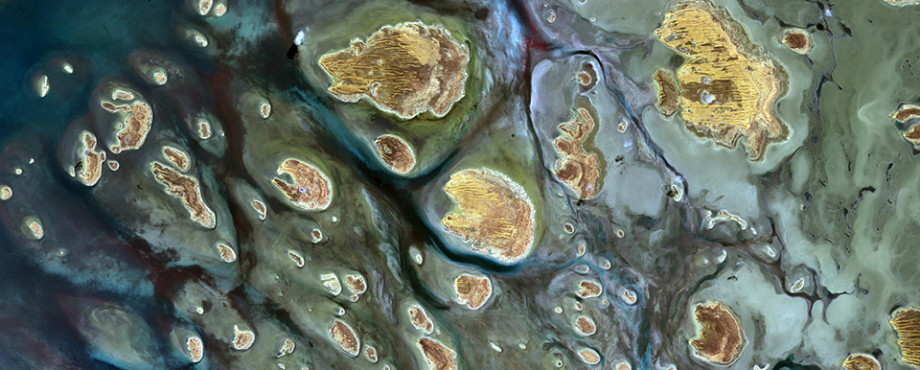 A group of sandy islands seen from above with dark green and blue water flowing around them.