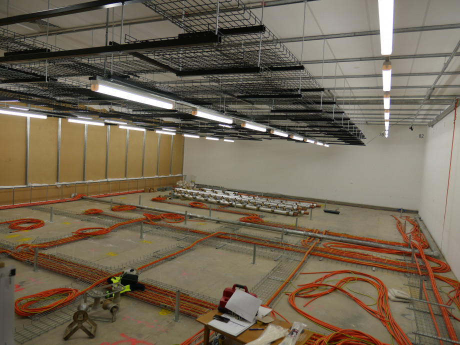A concrete floor covered with neatly arranged orange electrical cables, and some metal pipes lined up in rows.