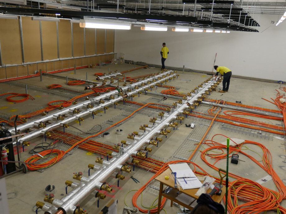 A concrete floor with neatly arranged orange electrical cables, now with long lines of metal pipes in place along the floor.