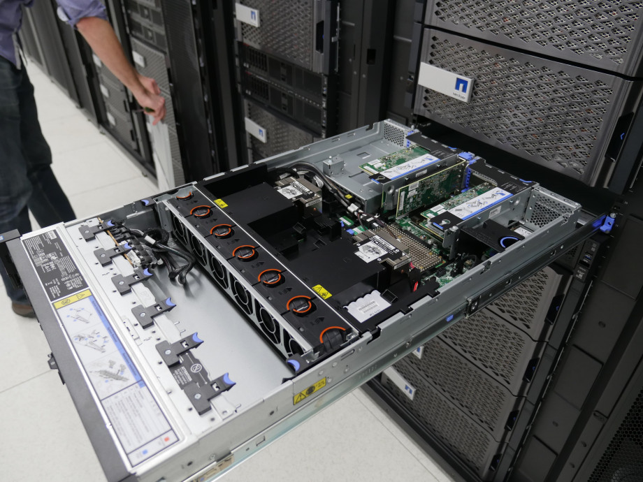 The inside of a computer server showing cabling, green motherboards and cooling units.