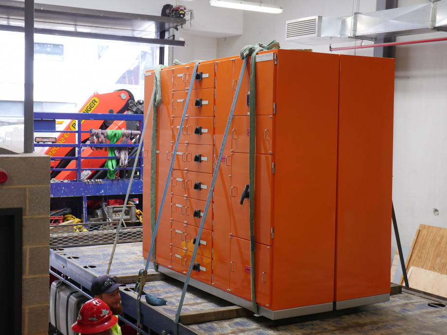 An orange metal box several metres wide and tall sits on the back of a flat bed truck.