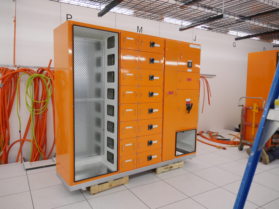 An orange metal box with opened compartments showing where electrical cables will connect.