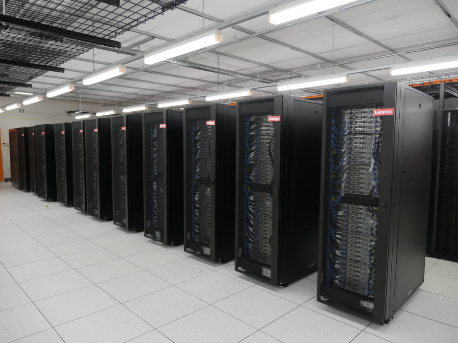 A long row of black and grey compute racks standing next to each other on a white floor.