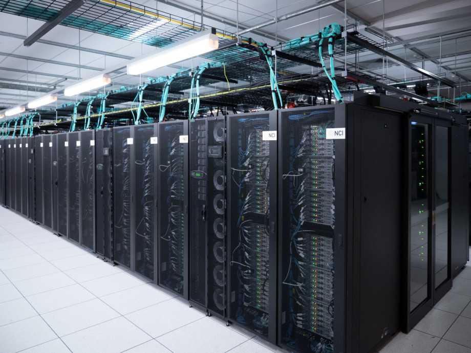 A row of black mesh cabinets with silver computer servers, cables and lights showing through.