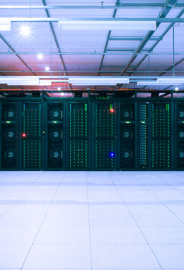 Green lights dotted across the front of a wide bank of dark servers in a darkened room.