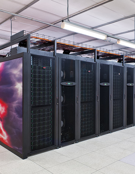 Looking at the corner of the supercomputer with rows of servers extending both ways to the edge of the picture.