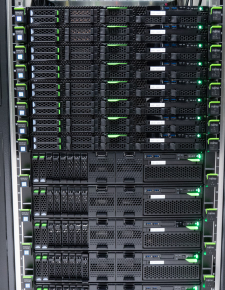 Black computer servers with green highlights stacked up on top of each other in a dedicated enclosure.