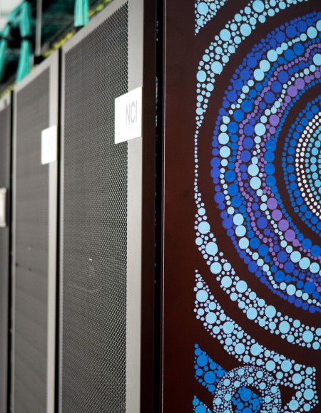Close-up view of the Gadi artwork with the long row of supercomputer servers visible in the background.