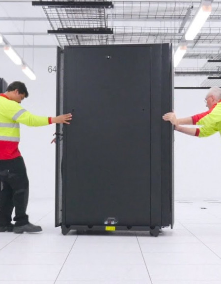 Two men roll a large black cabinet into position alongside other cabinets inside a large white room.