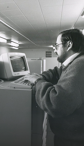Black and white image of man operating old computer terminal