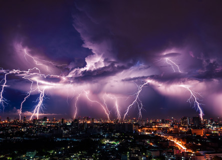 Ten bolts of lightning hitting a city in the distance, with purple illuminated clouds.