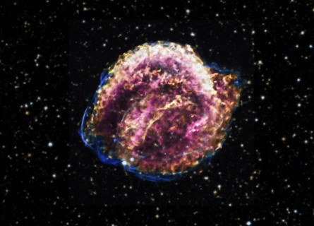 A purple, gold and pink ball of gas on a fuzzy black sky background filled with stars.