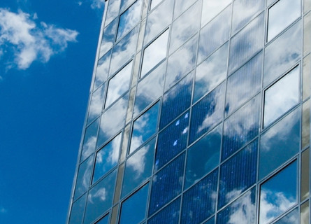 The glass windows of an office building reflecting blue sky and clouds.