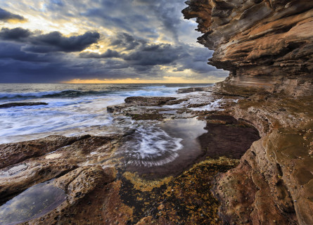 Striking clouds are a backdrop to swirling water in rock pools under layered rocky cliff walls.