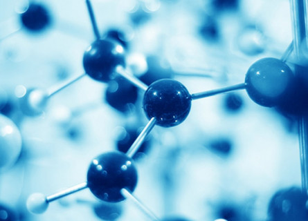 A blue tinted image of a ball and stick model of a molecule with many balls blurry in the foreground and background.