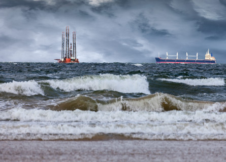 An oil rig and shipping container off shore from a beach while dark storm clouds approach.