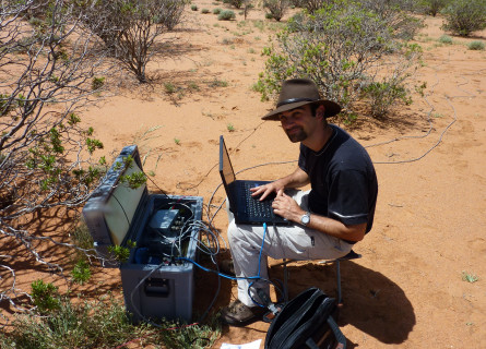Graham Heinson sits on a stool in the desert in front of computer and other technical scientific equipment.