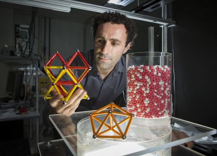 Mohammad Saadatfar holds a physical model of a molecule illustrating the packing study.