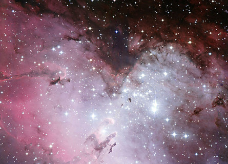 A pink and purple cloud of gas with a huge amount of bright and dim stars dotted around and through it.