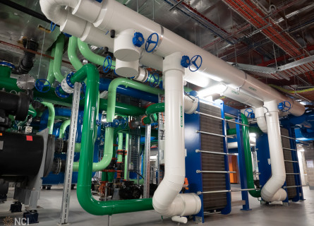 A complex series of green, blue and white pipes connected to tall blue and grey machines.