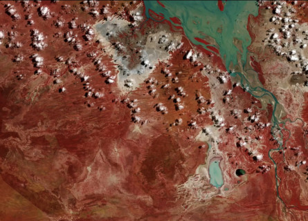 Screenshot from the Open Air video art project by Grayson Cooke. The video shows time lapse image sequences of the Australian landscape made using satellite imagery, interspersed with macro photography of paintings being created. The screenshot shows a river and lake in false colour blue, with lots of tiny clouds and the red outback.