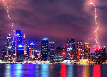 Two bolts of lightning strike a major city at night time. Lights of tall buildings are all visible and the whole image has a purple tint.