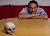 A human skull on a wooden table filling the frame, with a man behind the table leaning on it with arms crossed.