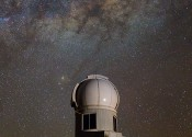 A round telescope dome sits on top of a hill under a brilliant night sky filled with thousands of stars in the Milky Way.
