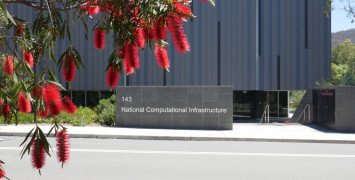 The front facade of NCI seen from the road, partially obscured by red callistemon flowers.