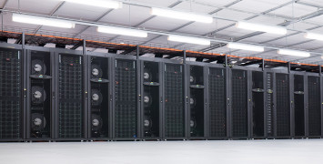 The NCI supercomputer Raijin, columns of black computer servers separated by stacks of in-row fans, in a big white room.