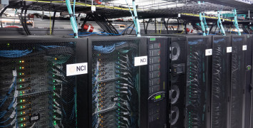 Black mesh cabinets with NCI logos on the front and computer servers, cables and lights visible inside them.